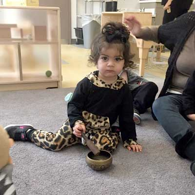 toddler sitting with singing bowl in yoga class
