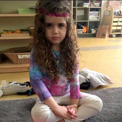 girl sitting cross-legged in yoga studio